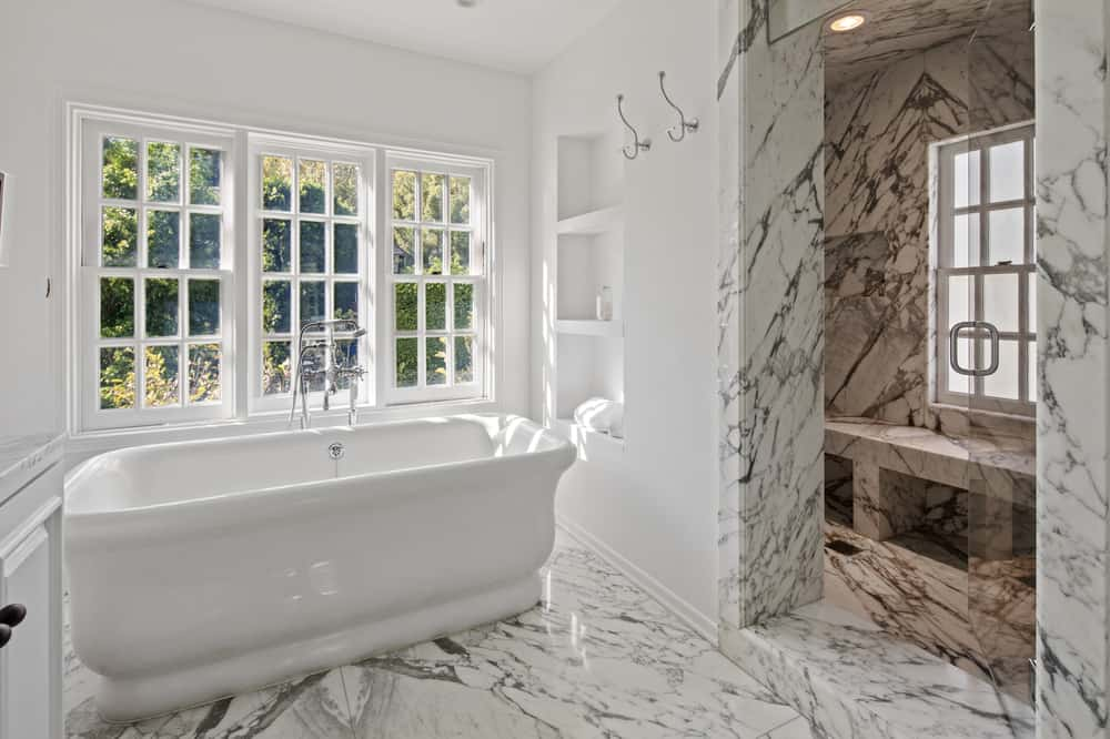 On the other side of the vanity and the freestanding bathtub is the entrance to the walk-in shower that has the same white marble material as the flooring. Images courtesy of Toptenrealestatedeals.com.