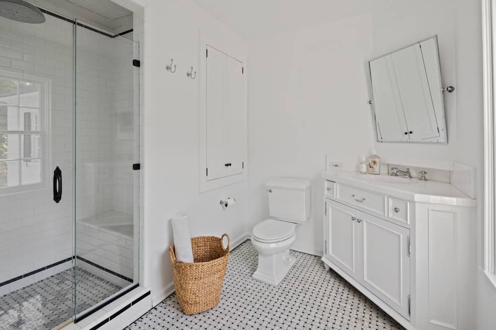 This simple bathroom has a rustic wicker basket for fresh towels. This bathroom is dominated by the bright white tones of the walls and vanity balanced by the flooring tiles as well as the glass-enclosed shower area. Images courtesy of Toptenrealestatedeals.com.