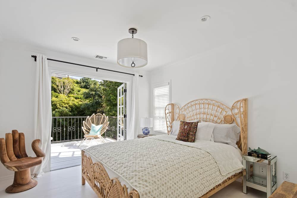 This bedroom has an abundance of natural lighting afforded by the wide wall that opens with French glass doors onto a balcony. It has a woven wicker bed that matches with the chair at the balcony. Images courtesy of Toptenrealestatedeals.com.