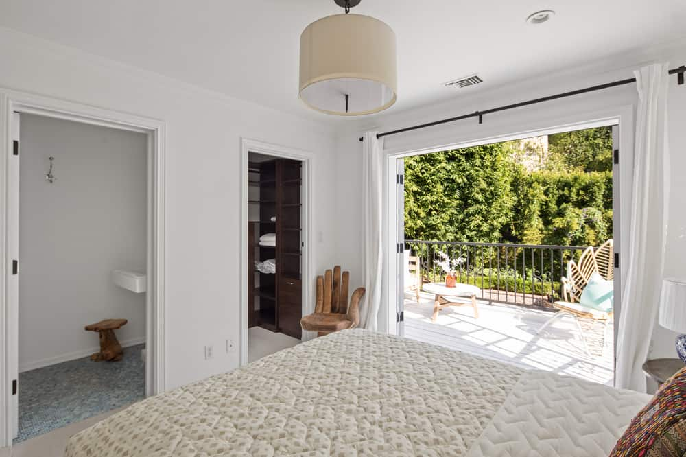 The large comfortable bed is topped with semi-flushmount lighting that hangs from the white ceiling. At the foot is the door leading to the walk-in closet and bathroom beside the wooden artistic chair. Images courtesy of Toptenrealestatedeals.com.