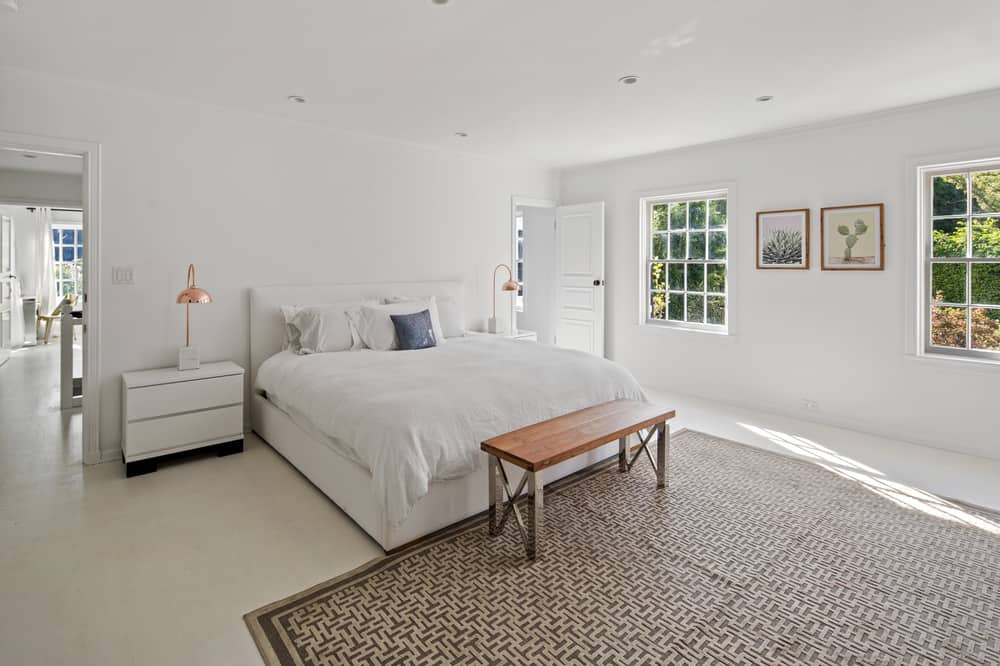 The large white bed of this bedroom is paired with white bedside drawers topped with brass table lamps that matches with the wood-top metal bench at the foot of the bed. Images courtesy of Toptenrealestatedeals.com.