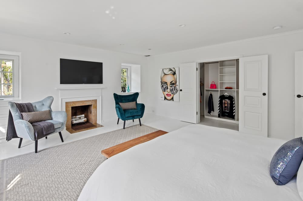 Across from the bed is the fireplace with a wall-mounted TV above it and a green cushioned armchair that stands out against the bright white walls. Images courtesy of Toptenrealestatedeals.com.