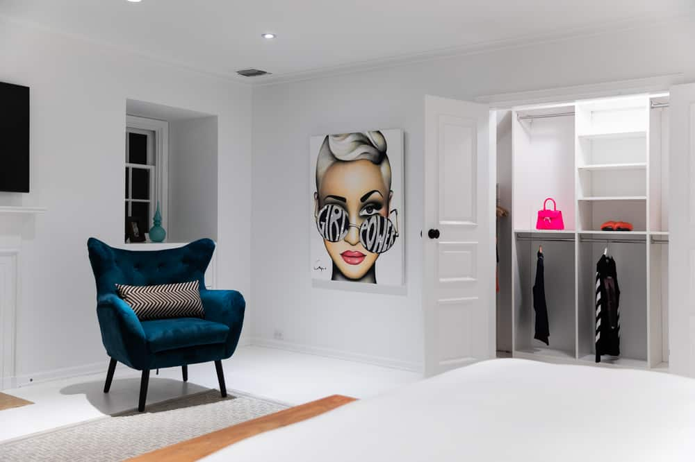This plush green velvet arm chair is adorned on the side with a large cool painting of a woman. Beside that is the door leading to the large closet. Images courtesy of Toptenrealestatedeals.com.