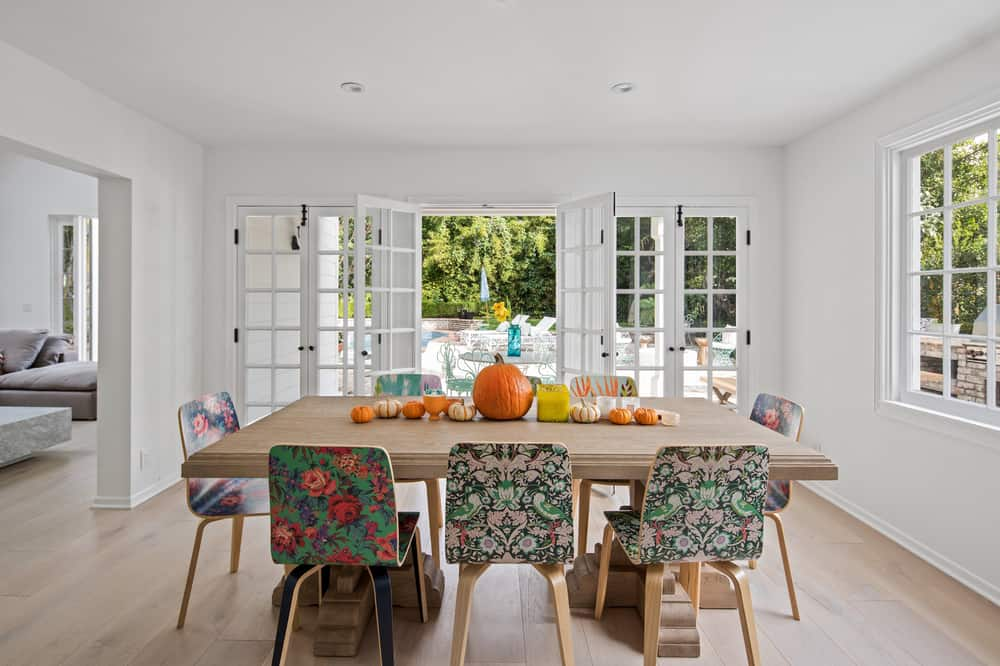 The various colorful and patterned dining chairs stand out against the simple hues of the dining room along with the colorful fall-themed centerpiece on the table. Images courtesy of Toptenrealestatedeals.com.