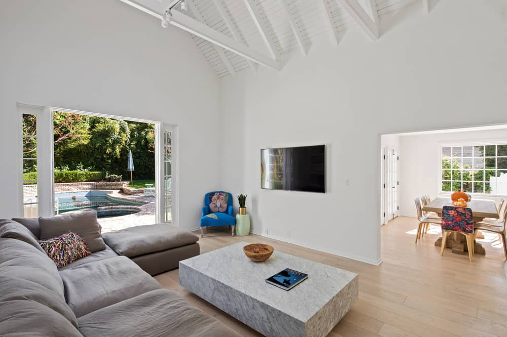 Across from the large L-shaped sectional sofa and the coffee table is the wall-mounted TV that stands out against the white wall matching well with the white arched ceiling with exposed beams. Images courtesy of Toptenrealestatedeals.com.