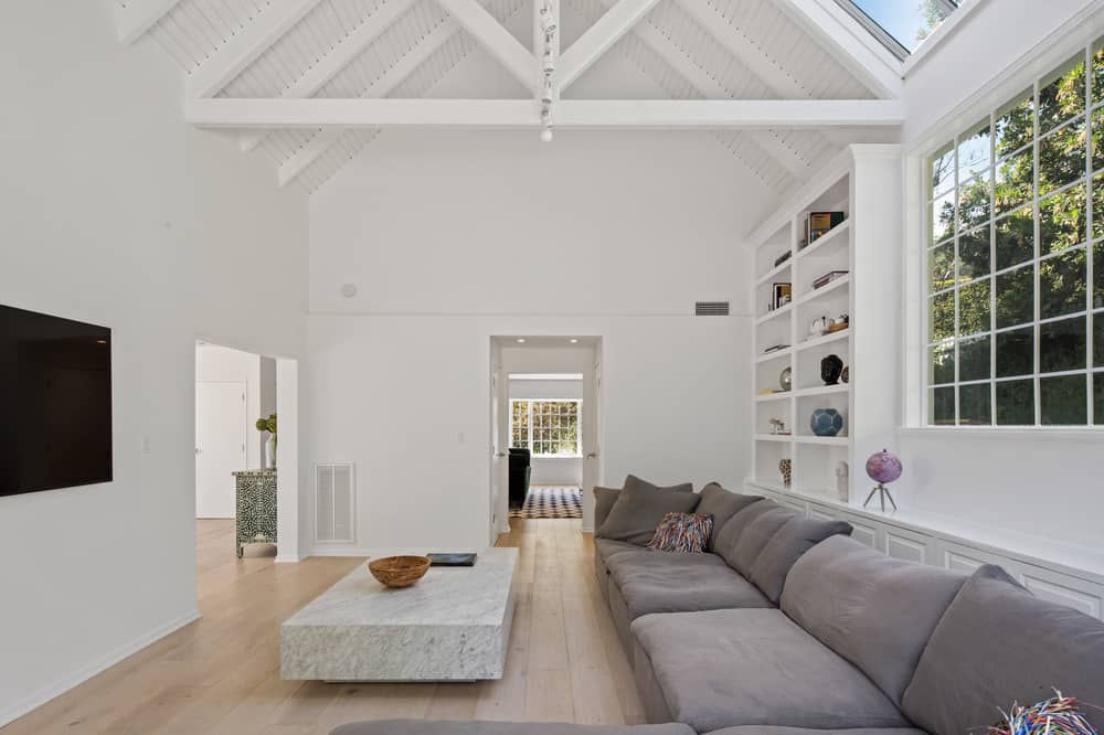 This view shows more of the gorgeous exposed wooden beams of the arched ceiling as well as a large built-in shelving behind the L-shaped sectional sofa. Images courtesy of Toptenrealestatedeals.com.