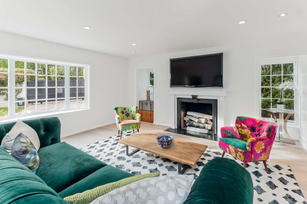 The bright and airy white living room of the traditional home is complemented by the green velvet couch as well as the pair of colorful cushioned arm chairs. Images courtesy of Toptenrealestatedeals.com.