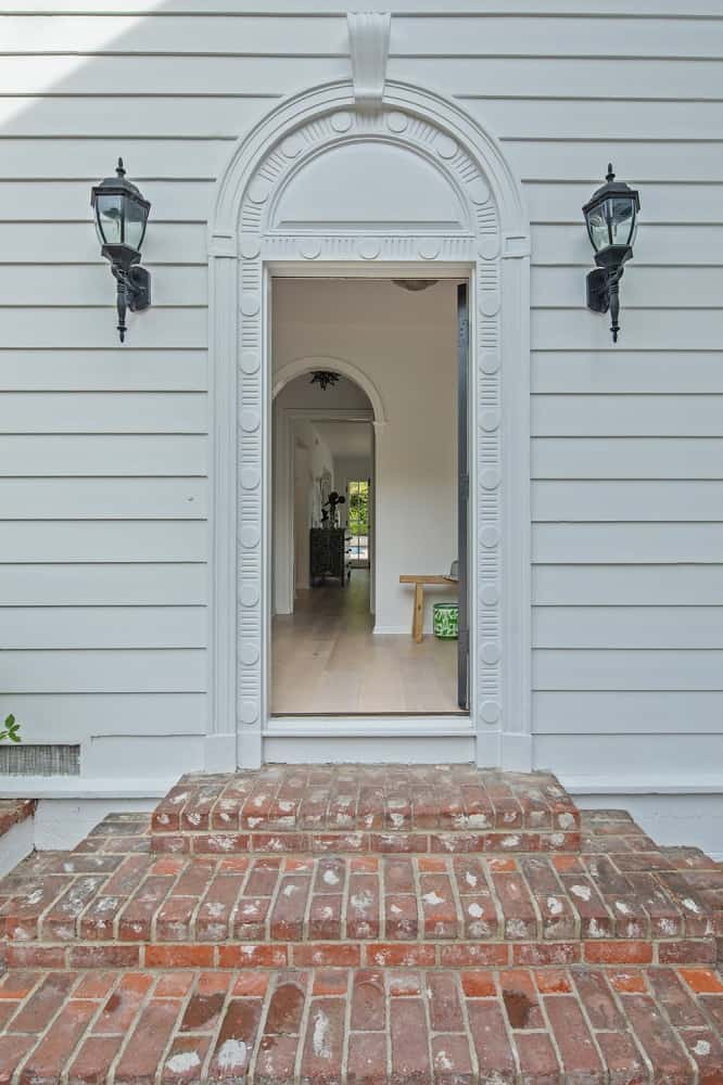 This is the main entry with a small red brick step and entryway flanked by charming wall-mounted lamps that bring character to the simple white walls. Images courtesy of Toptenrealestatedeals.com.