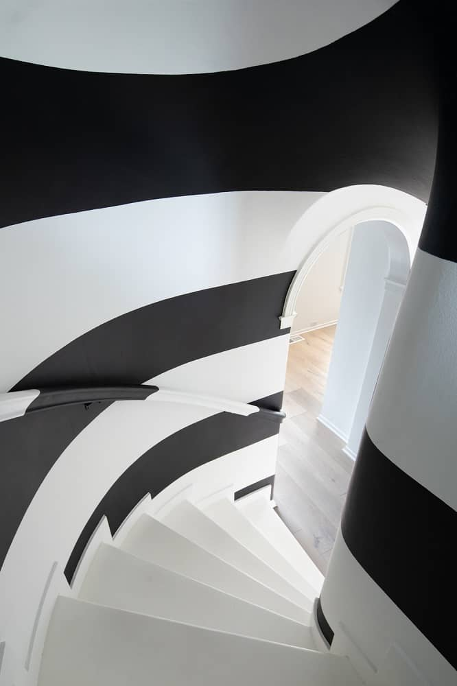 The quirky spiral staircase of the home has striped of black and white for a unique aesthetic to pair the white steps and arched entryways. Images courtesy of Toptenrealestatedeals.com.