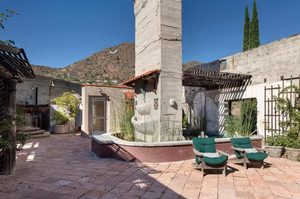 This rooftop outdoor area has rough terracotta walkways that makes the green chairs stand out as well as the various potted plants. In the middle of this area is a large stone structure turned into a beautiful pond and fountain. Images courtesy of Toptenrealestatedeals.com.