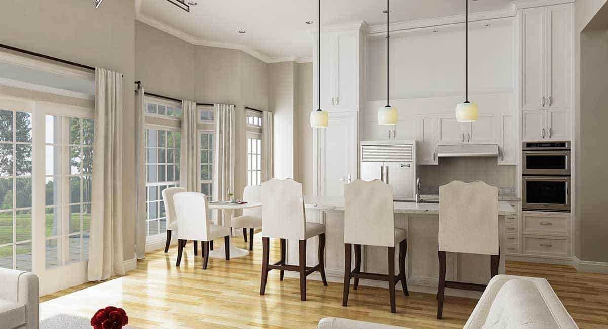 The kitchen features a neutral palette softened by the hardwood flooring. It has a marble top island and a round dining set sitting next to the white framed windows.