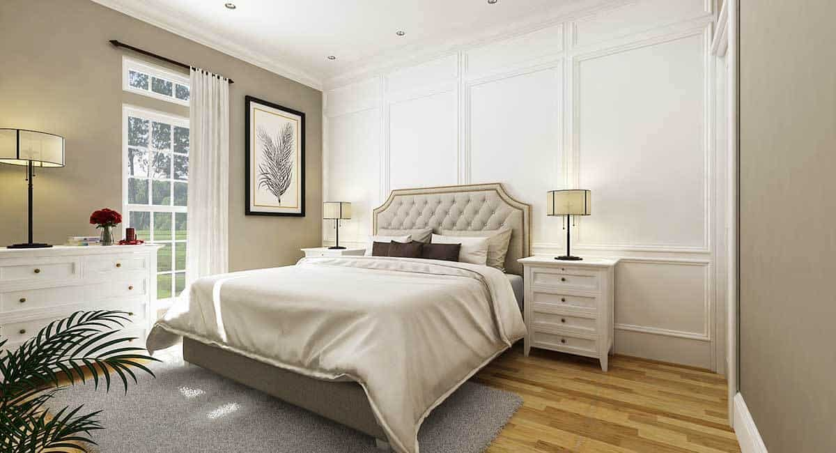 The bedroom is painted with a darker shade of gray. White wainscoted walls serve as a sleek backdrop to the tufted bed and nightstands.