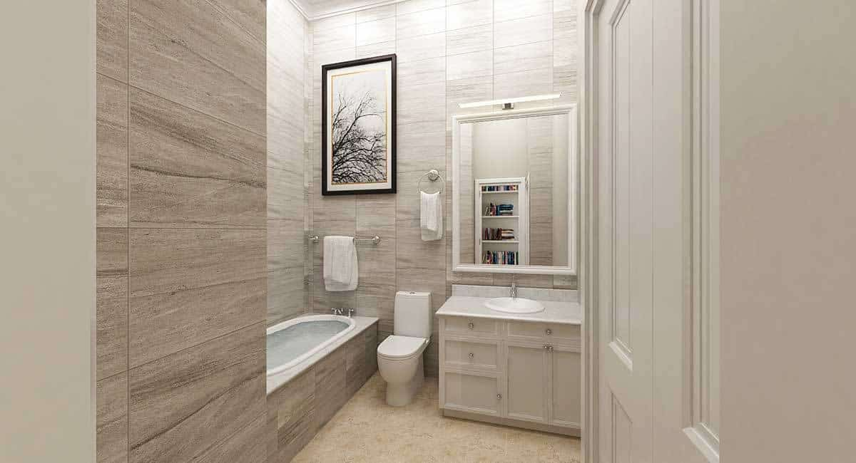 This bathroom is filled with a drop-in tub, a toilet and a sink vanity paired with a large mirror. Branch artwork against the tiled walls adds a charming accent.