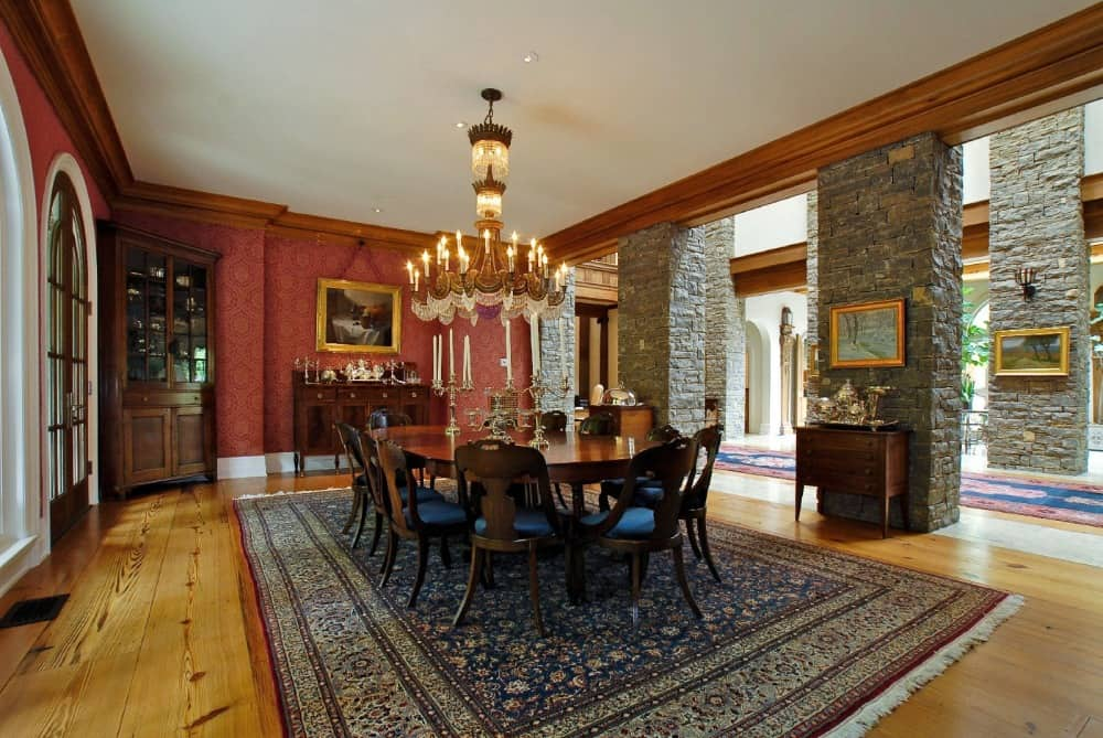 The mansion's formal dining room boasts a classy oval-shaped dining table and chairs set lighted by a grand chandelier that looks absolutely glamorous. Images courtesy of Toptenrealestatedeals.com.