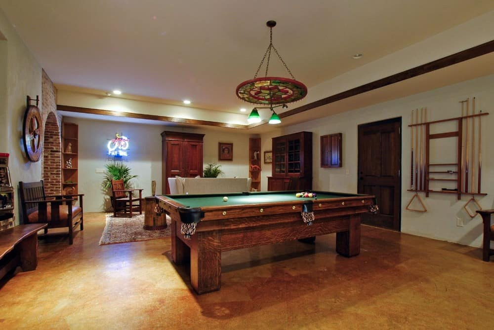 Another focused look at the game room's classic billiards table lighted by a stylish ceiling light. Images courtesy of Toptenrealestatedeals.com.