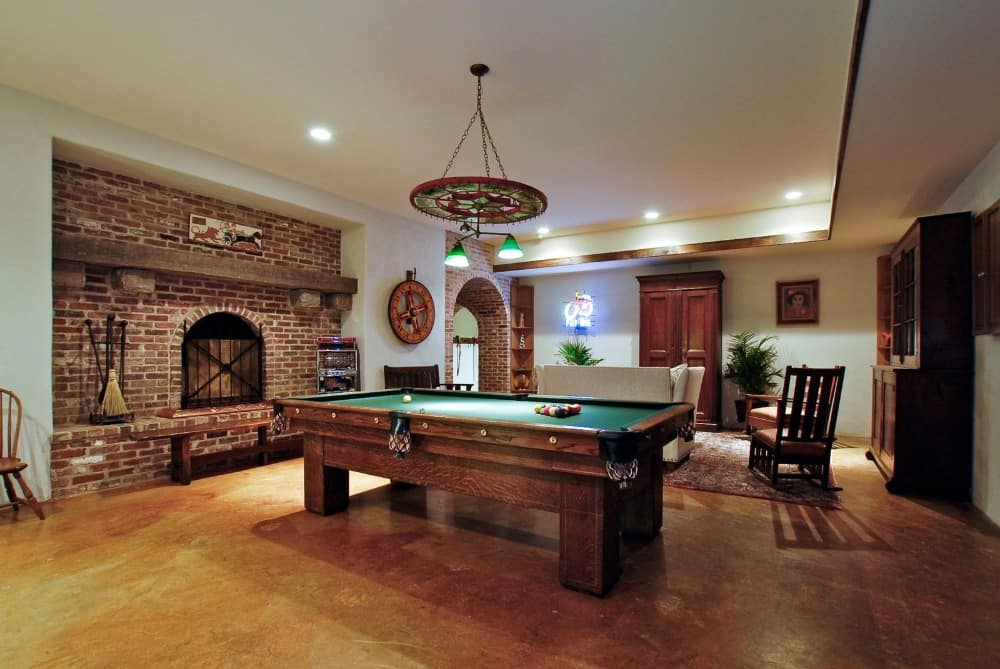 Another look at the game room focusing on the billiards table set near the brick fireplace on the side. Images courtesy of Toptenrealestatedeals.com.