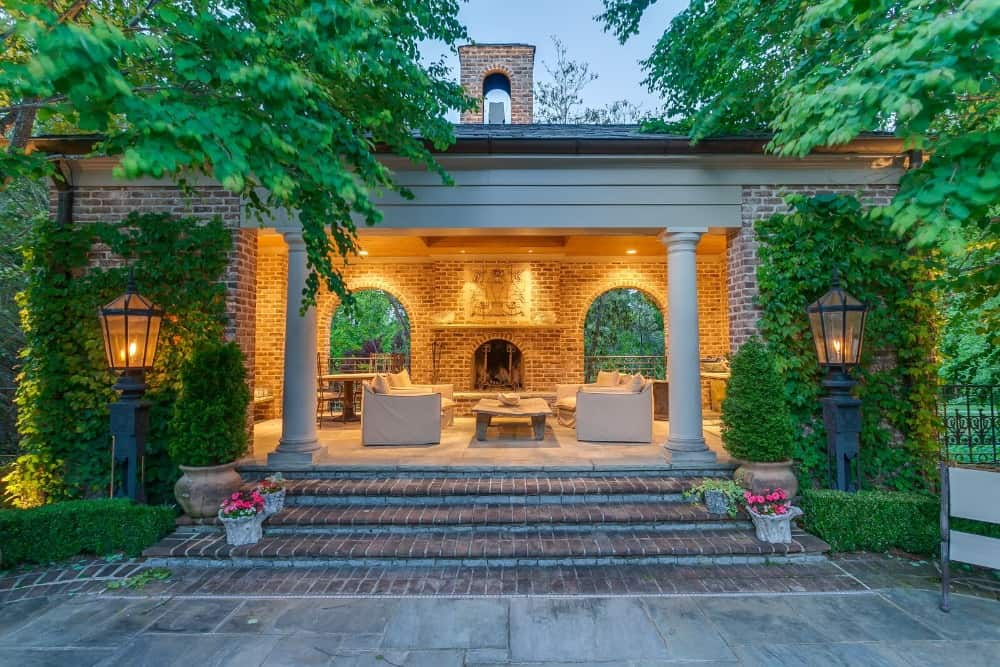 A look at the home's outdoor living space featuring a nice sofa set with a brick fireplace. Images courtesy of Toptenrealestatedeals.com.