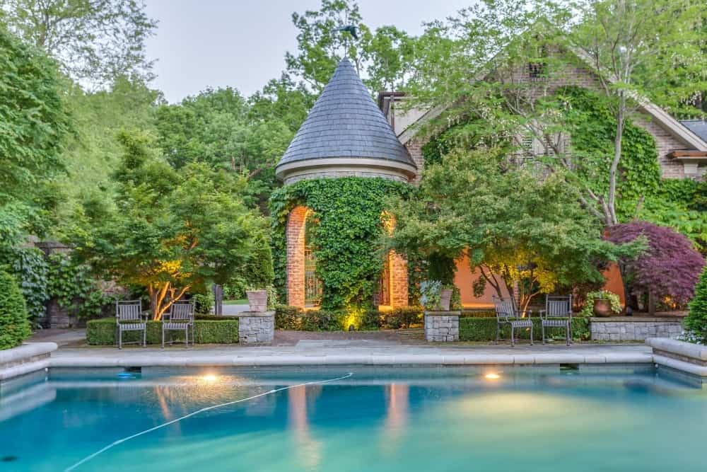 A side view of the mansion's swimming pool set at the backyard surrounded by the lovely garden. Images courtesy of Toptenrealestatedeals.com.