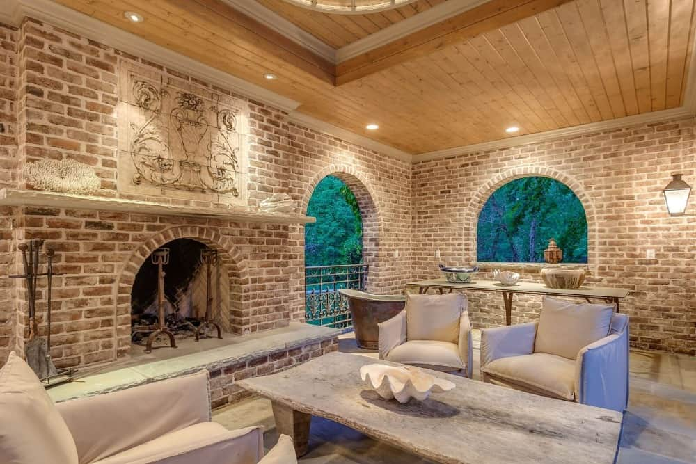 Another one of the living spaces featuring a nice set of seats with a rectangular rustic center table set near the large brick fireplace. Images courtesy of Toptenrealestatedeals.com.