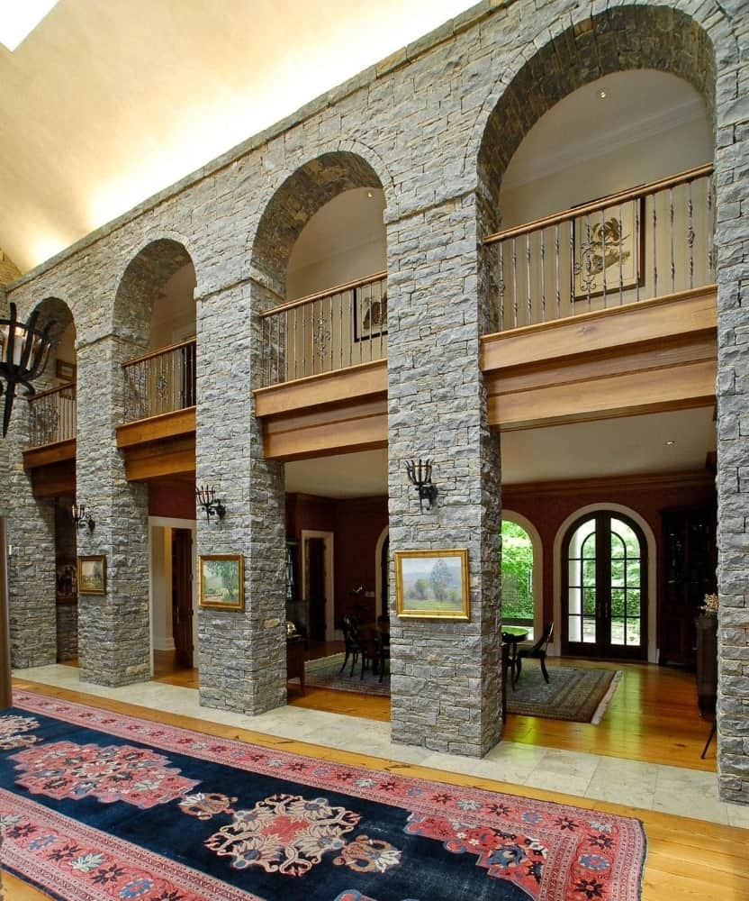 The hallway features stone pillars lighted by wall lights and has portrait wall decors. Images courtesy of Toptenrealestatedeals.com.