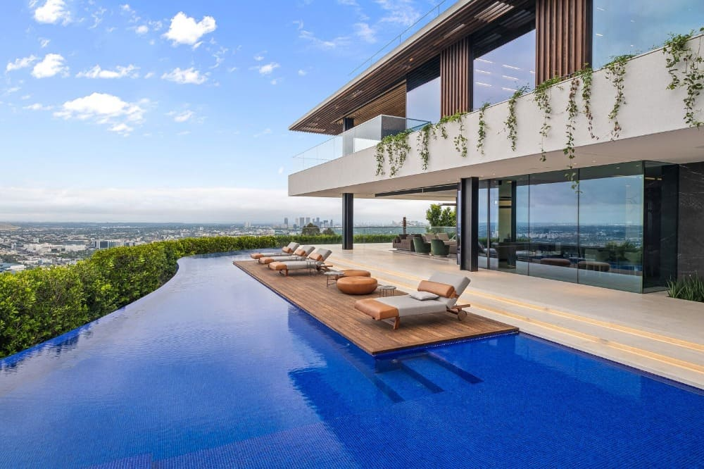 A look at the home's custom infinity swimming pool showcasing the blue tiles flooring and the deck where the sitting lounges are set. Images courtesy of Toptenrealestatedeals.com.