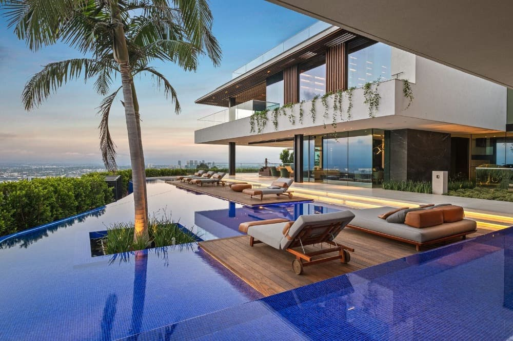 Outdoor view of the house boasting its stunning custom infinity pool and sitting lounges on the deck. Images courtesy of Toptenrealestatedeals.com.