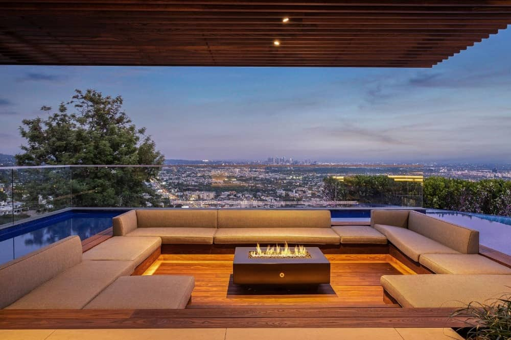 An outdoor living with modern seats and a stylish fire pit. The area is surrounded by the custom swimming pool. Images courtesy of Toptenrealestatedeals.com.