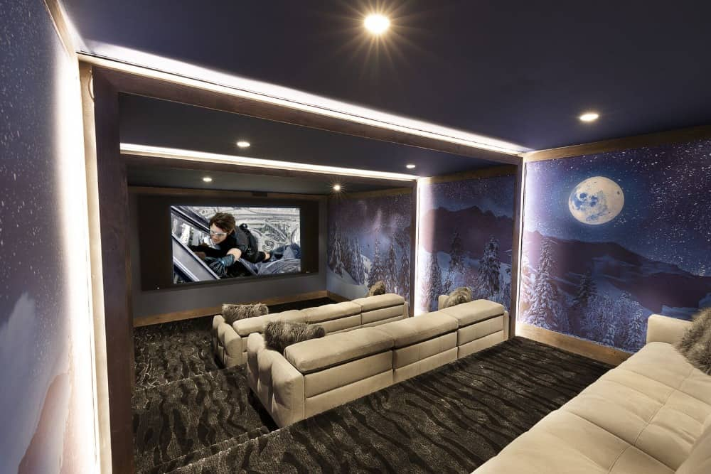 The home theater features stunning wall designs and stylish carpet flooring. The room offers sectional sofa sets along with nice ceiling lighting. Images courtesy of Toptenrealestatedeals.com.