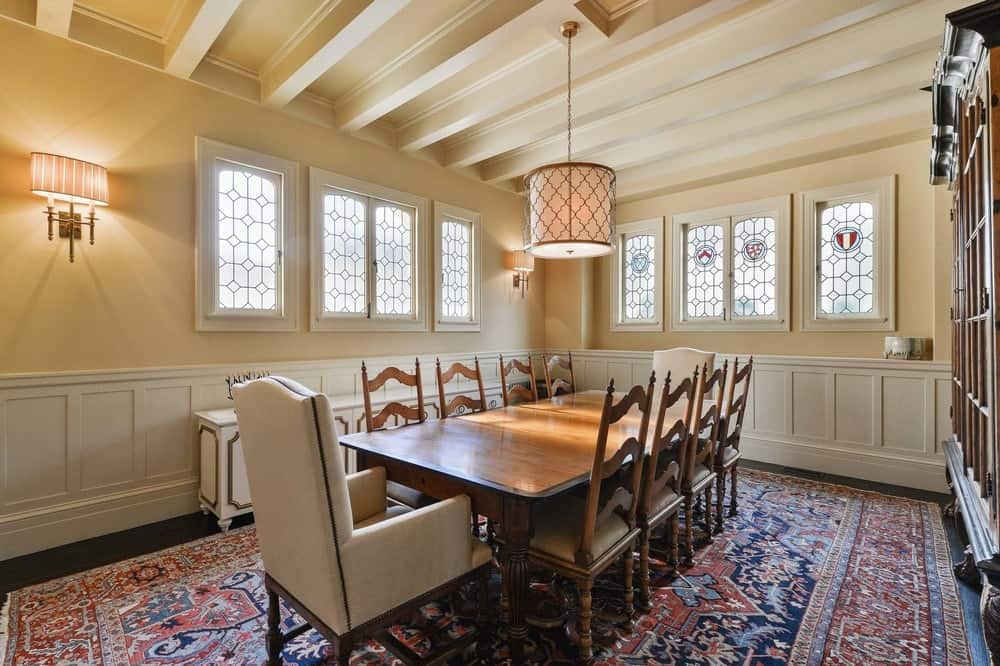 The formal dining room has a dark hardwood flooring that is dominated by the large colorful patterned area rug contrasting the bright beige walls that are lined by a row of beautiful stained glass windows. Images courtesy of Toptenrealestatedeals.com.