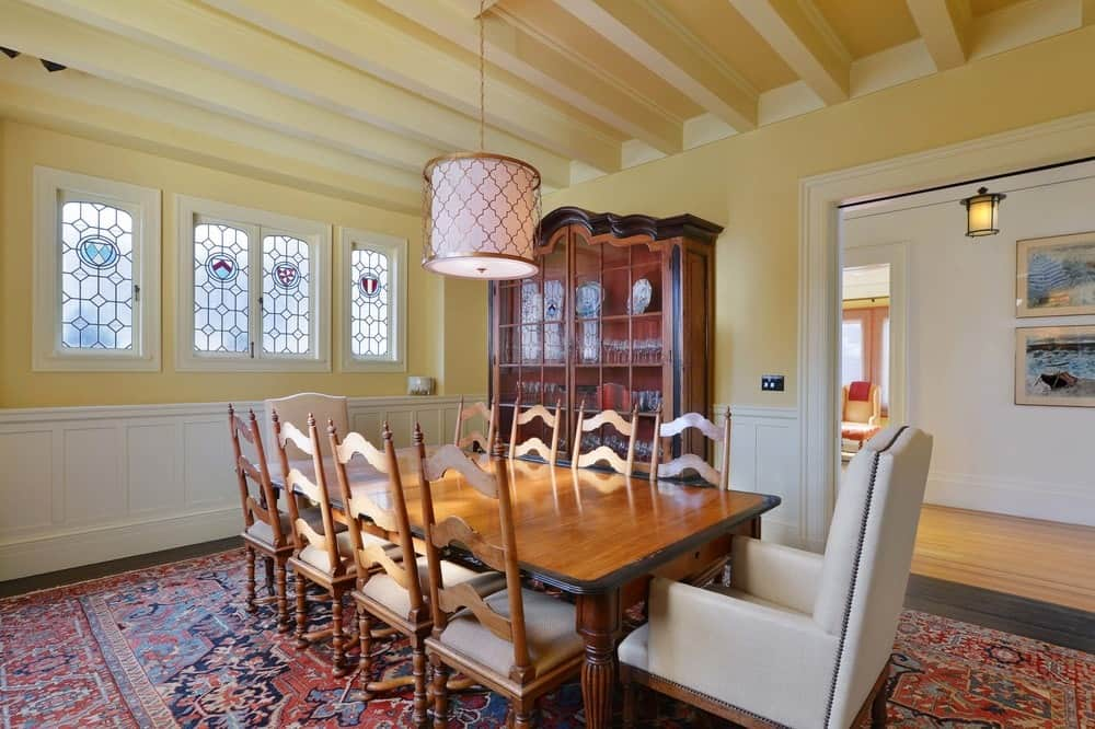 The dining room has a large rectangular wooden dining table that matches with its wooden dining chairs as well as the dining room cabinet placed on the beige wall by the entrance making it stand out against the beige walls, especially with the white wainscoting. Images courtesy of Toptenrealestatedeals.com.