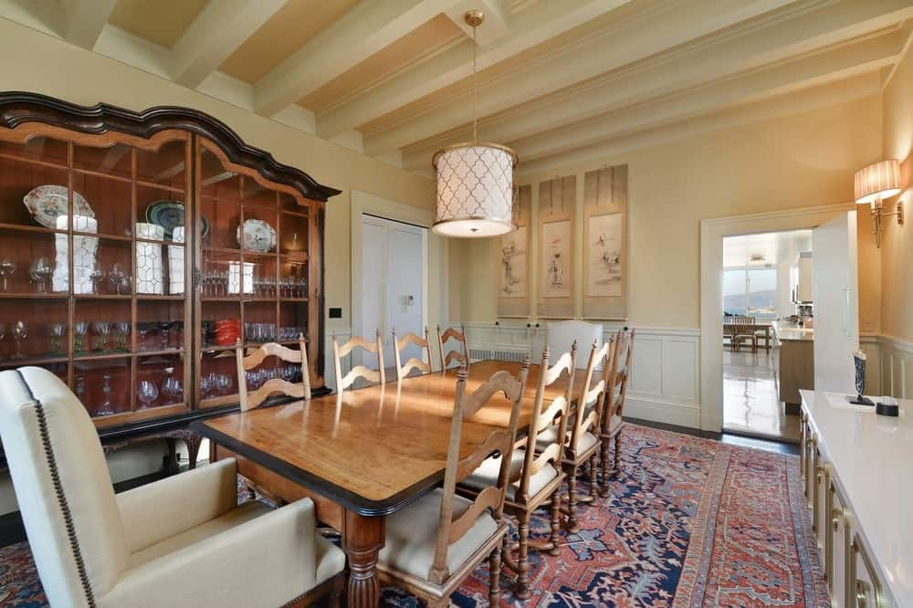 Each head of the large wooden dining table is complemented by a beige cushioned arm chair that fits perfectly with the surrounding wainscoting of the beige walls. topped with a lovely pendant light hanging from the beige ceiling. Images courtesy of Toptenrealestatedeals.com.