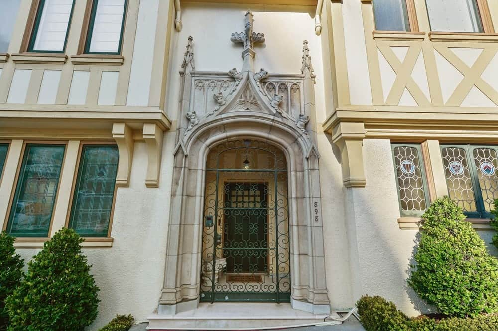 This is a close-up view of the main entryway that is topped with a majestic stone arch with lovely details making it look like an entrance to a church. There is also a wrought gate for security purposes. Images courtesy of Toptenrealestatedeals.com.