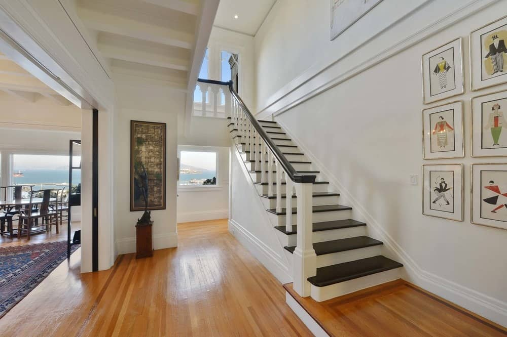 Upon entry, you are welcomed by this charming foyer that has rich hardwood flooring to complement the bright beige walls and white molding. Images courtesy of Toptenrealestatedeals.com.