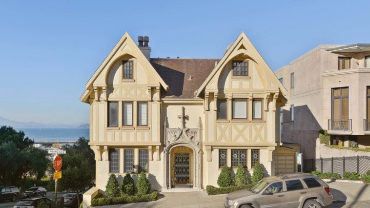 This Tudor Revival home has gorgeous beige exteriors with minute architectural details that give the exteriors a unique character. The front of the house is adroned with a couple of plant boxes with shrubs to complement the exteriors. The two A-frame roofs of the house towers over the inclined street below. Images courtesy of Toptenrealestatedeals.com.