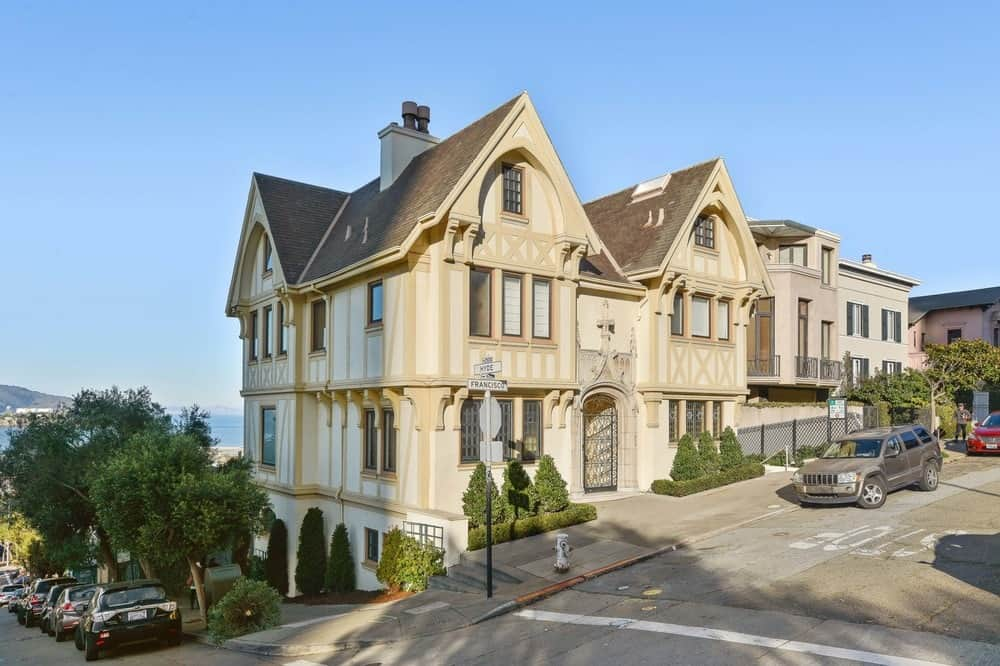 This view of the home shows that it is located on a corner lot and the sides of the beige exterior walls are adorned by planted shrubs that bring color and character to the concrete sidewalk. Images courtesy of Toptenrealestatedeals.com.