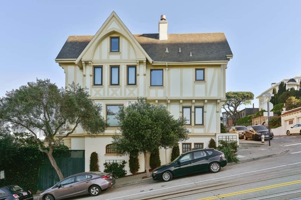 This is the side view of the house on the side of a road with a steep incline. The house stands out in this corner of the neighborhood with its towering A-frame roof and bright beige exteriors adorned with trees and sbrubs on the side. Images courtesy of Toptenrealestatedeals.com.