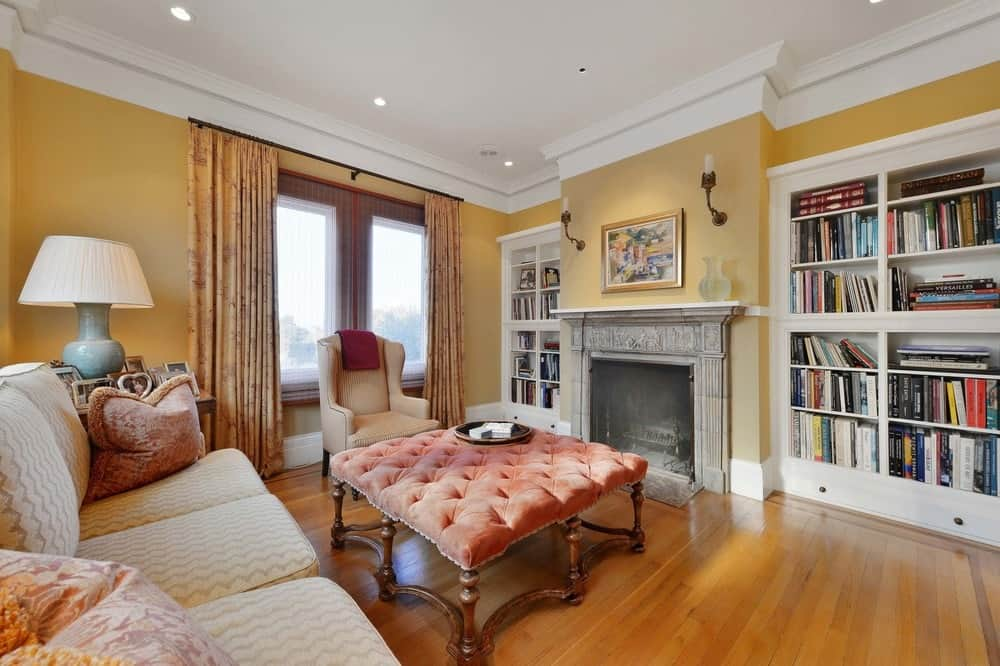Across from the couch is a warm fireplace that has a gray mantle making it stand out against the beige wall. This mantle is flanked by built-in white book shelves and topped with a painting and wall-mounted lamps. Images courtesy of Toptenrealestatedeals.com.