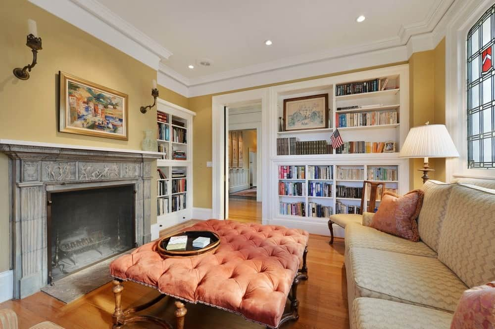 The side wall by the entrance is also dominated by a large white wooden book shelf built into the wall filled with books and decors. This pairs well with the white ceiling that is lined with charming white moldings. Images courtesy of Toptenrealestatedeals.com.