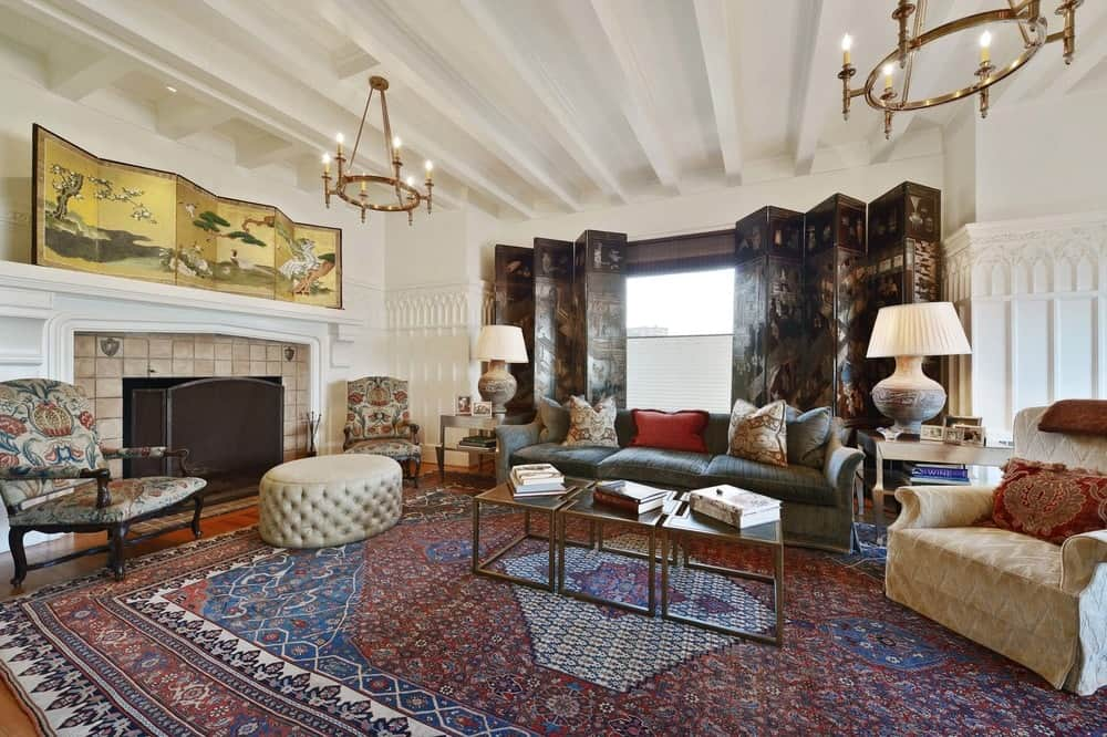 The spacious and airy living room has bright walls and matching ceiling with exposed wooden beams and a round chandelier. This is contrasted by the colorful patterned large area rug that dominates the hardwood flooring. Images courtesy of Toptenrealestatedeals.com.