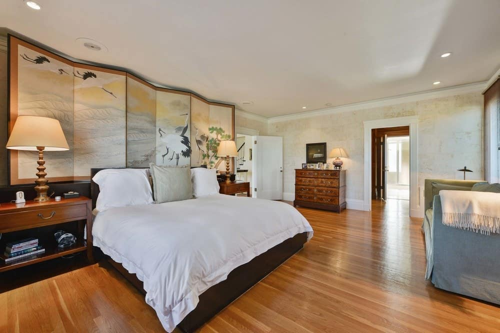 The large primary bedroom has hardwood flooring that matches with the dresser as well as the bedside tables flanking the dark brown bed with white sheets. The headboard of this bed is topped with a large folding artwork piece with charming Asian designs. Images courtesy of Toptenrealestatedeals.com.