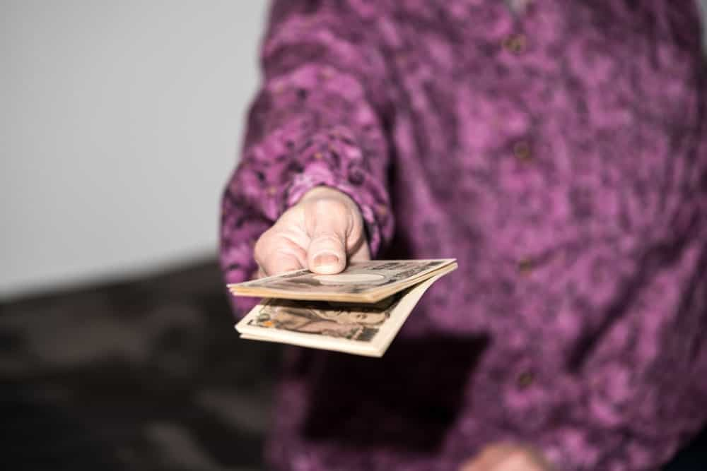 Old woman holding money.