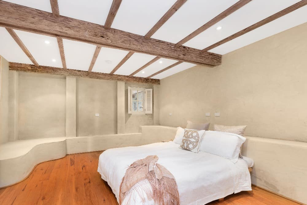 Another bedroom suite featuring hardwood flooring and a ceiling with rustic beams. Images courtesy of Toptenrealestatedeals.com.