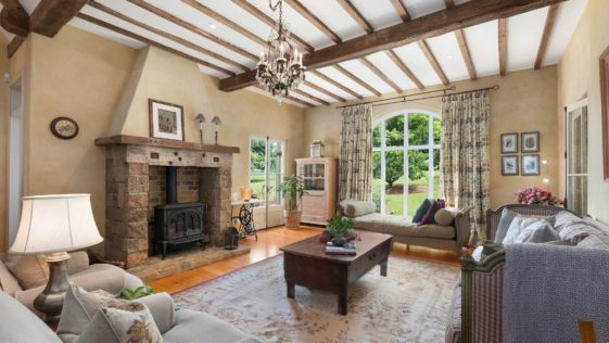 Large formal living room featuring a cozy sofa set and a classy fireplace, along with a ceiling with exposed wooden beams.