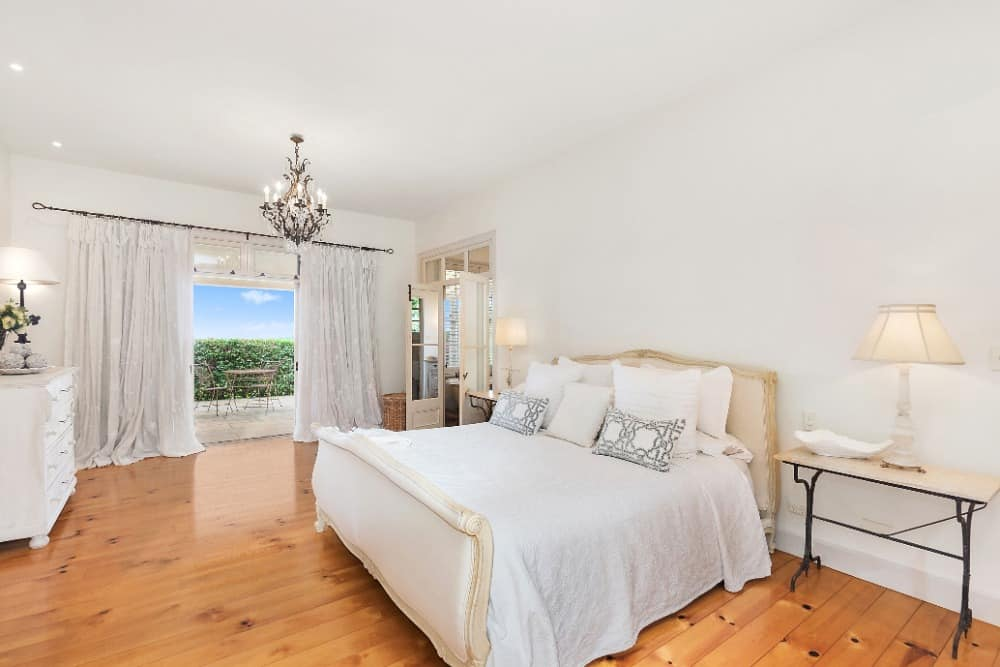 Another bedroom suite with a large and lovely bed setup lighted by table lamps. The room is lighted by a gorgeous chandelier together with recessed lights. There's a personal bathroom and a balcony with a table set. Images courtesy of Toptenrealestatedeals.com.