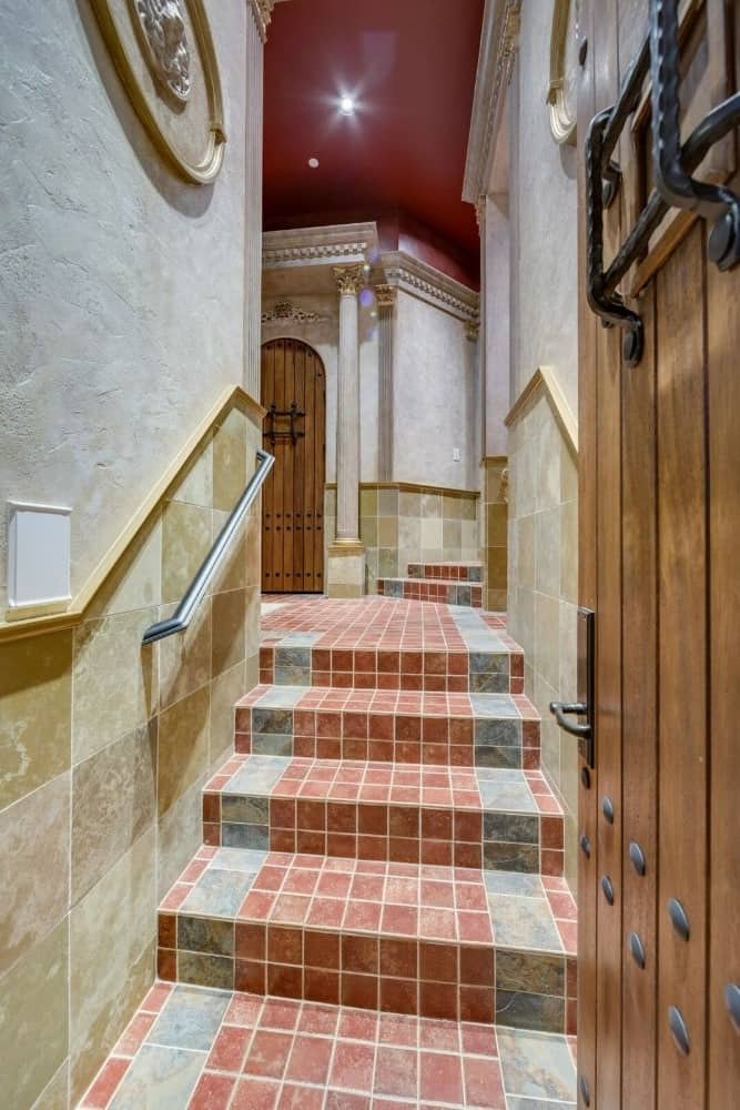 This hallway leads to the bathroom with gorgeous Romanesque wall designs and a red ceiling. Images courtesy of Toptenrealestatedeals.com.