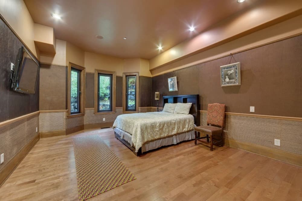 This bedroom suite features stylish walls and hardwood flooring, along with a cozy bed setup and a widescreen TV set in front. Images courtesy of Toptenrealestatedeals.com.