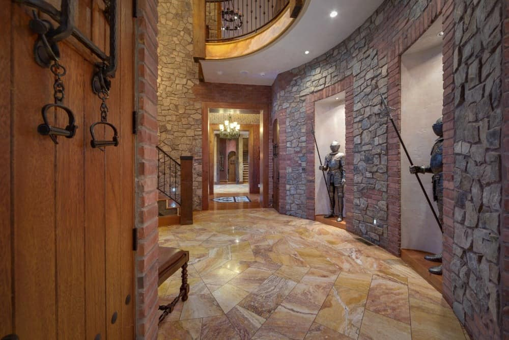 The foyer boasts Medieval armored soldiers as decorations, along with classy tiles flooring and stone walls. Images courtesy of Toptenrealestatedeals.com.