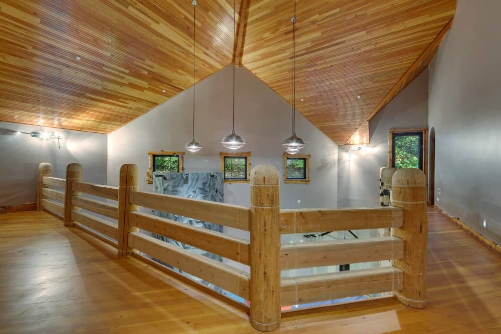 The second floor features hardwood flooring and wooden railings, along with a wooden ceiling. Images courtesy of Toptenrealestatedeals.com.