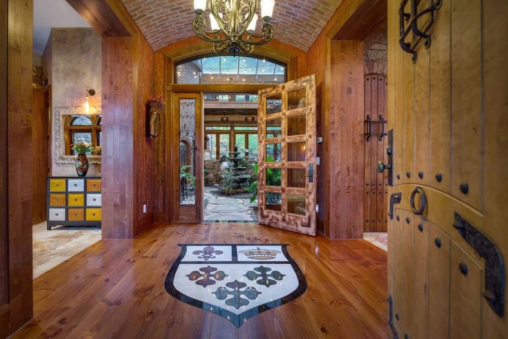 This hallway leads to many indoor amenities. It also features gorgeous decorated hardwood flooring and a chandelier ceiling light. Images courtesy of Toptenrealestatedeals.com.