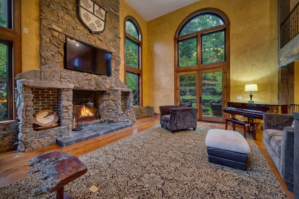The formal living room boasts a cozy gray sofa along with a large stone fireplace with a widescreen TV set just above it. Images courtesy of Toptenrealestatedeals.com.